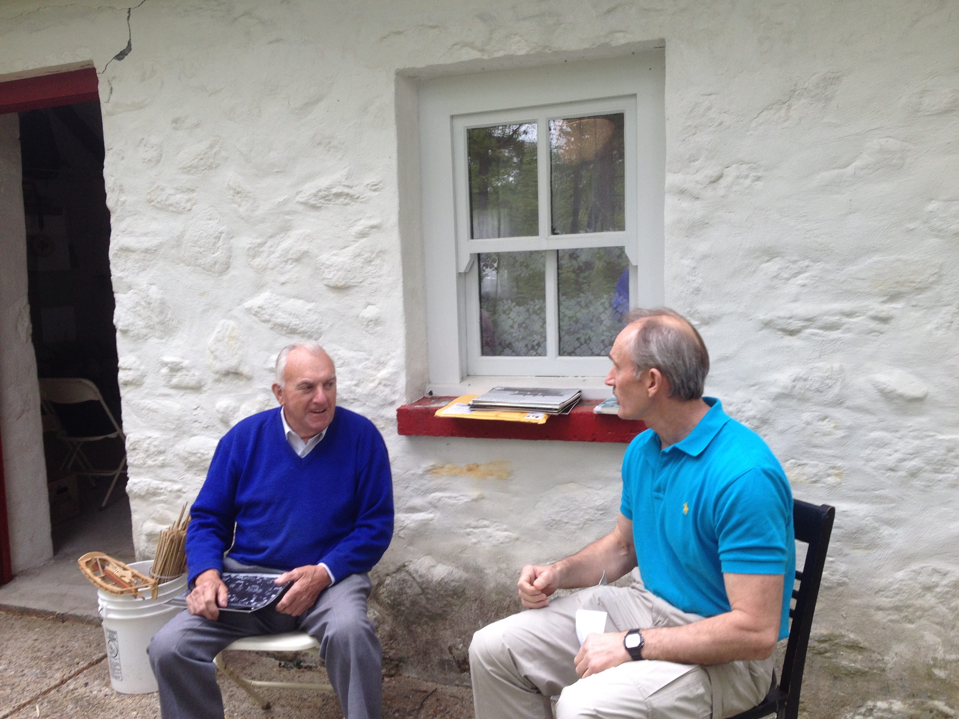 Mike Newell interviewing Johnny Joyce the morning of May 21, 2016, at the Irish Cottage, Irish Cultural Centre 200 New Boston Drive, Canton, MA. Two men seated. Man on left wearing purple shirt and gray pants, man on right wearing blue polo shirt and khaki pants.