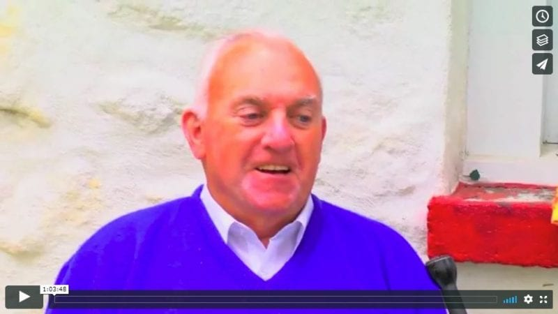 Screenshot from interview with Johnny Joyce, 2016. Head and shoulders image of man wearing purple sweater over white collared shirt.