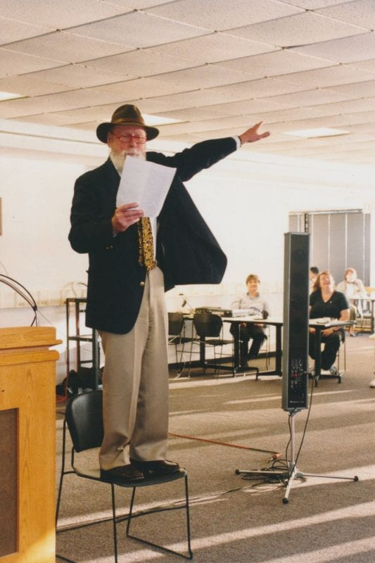 Professor Duncan Nelson stands on a chair and recites an ode at the 1999 Years of Service event.