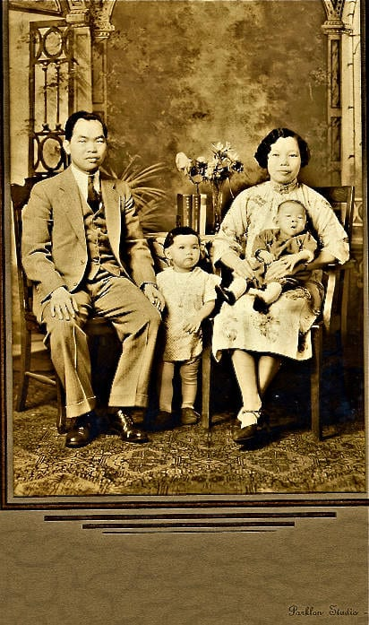 'This photo was taken in a studio in Boston, Massachusetts in 1934. My dad Edwin Keyseu Chin, 30, and my mom Mary Gee, 24, my oldest sister Helen, 1.5, and my oldest brother Tom, 6 months. This is two years after mom came to Boston from Zoishan, China and married Dad. They operated a hand laundry in Charlestown, Massachusetts near City Square in the shadow of the elevated train tracks. Charlestown at the time was mostly Irish. Pictured, from back to front, left to right: my father Edwin Keyseu Chin, my mother Mary Gee Chin, my sister Helen Chin, and my brother Tom Chin.'