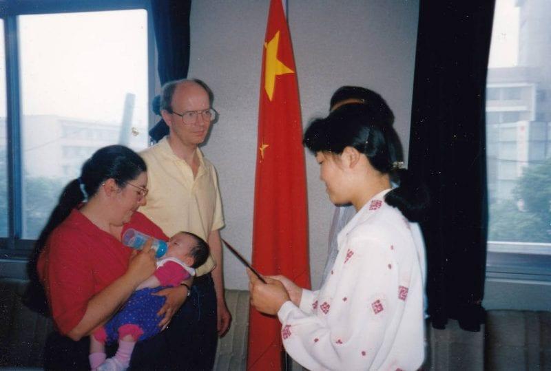 'This photo depicts the official moment when I was adopted. I am being held and fed a bottle as a seven-month year old baby by my mom, Marjorie, while my dad, Doug, looks on. Two government officals are holding some certificate. A Chinese flag is in the background, representing the place and national affliation. I would like to know the exact location, date, time, but I just didn't ask my parents this morning. Hdl.handle.net/11603/10862'