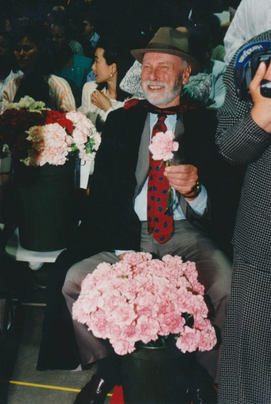 Professor Duncan Nelson sits with a bunch of light pink carnations, holding one in his hand.