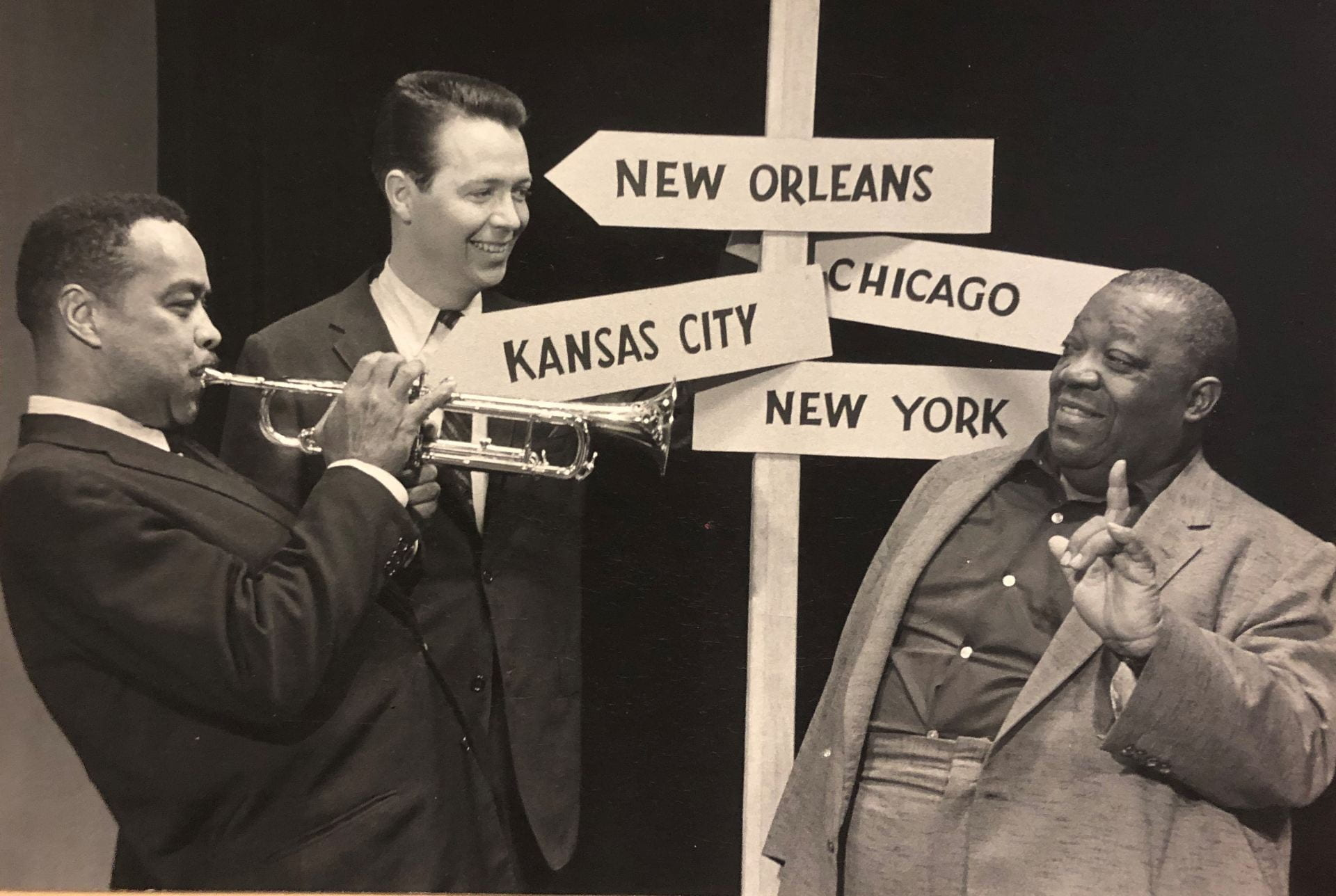 Black and white photograph from 1958 depicting radio announcer James Townsend Fitch standing with jazz musicians Clark Terry and Jimmy Ruching in front if a post with arrowed signs each labeled New Orleans, Kansas City, Chicago, and New York