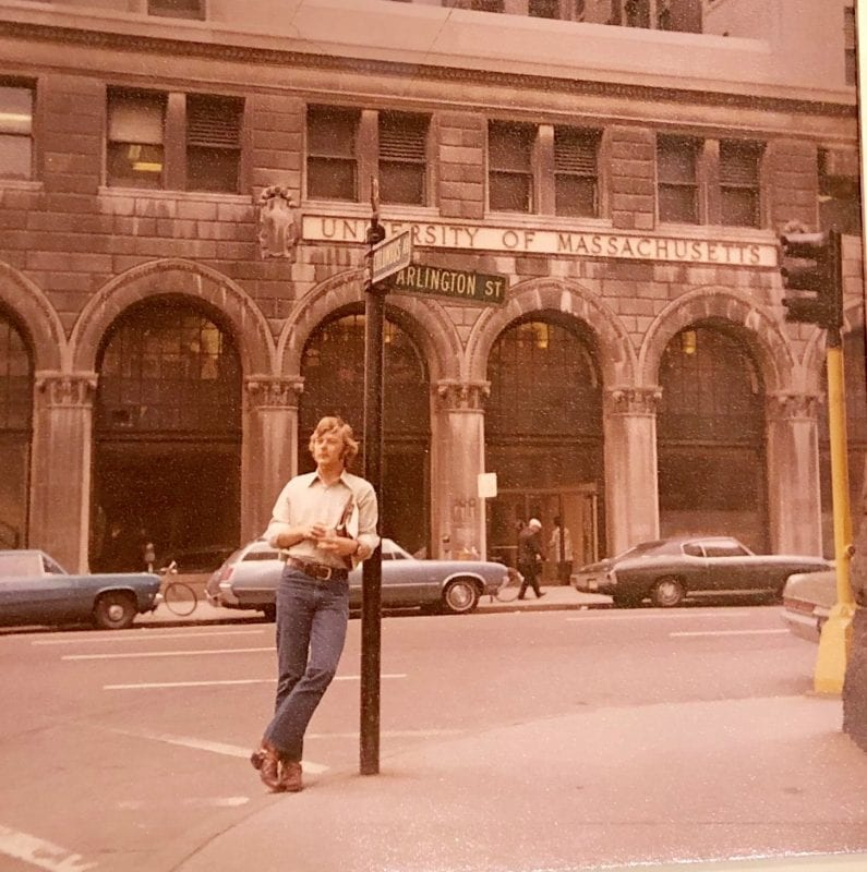 Man leans against a pole with street signs for Arlington Street and Columbus Avenue in front of a University of Massachusetts building