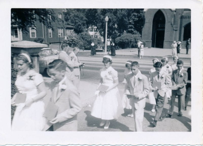 'My eighth grade graduation in 1957 from Saint Mary's School in Winchester--church in background. Pictured: myself Anne Hurley (central figure, girl in white gress, lamp post sticking out of her head).'