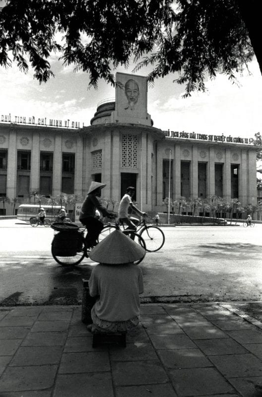 Woman sits on a sidewalk and people ride bicycles in front of the Central Bank