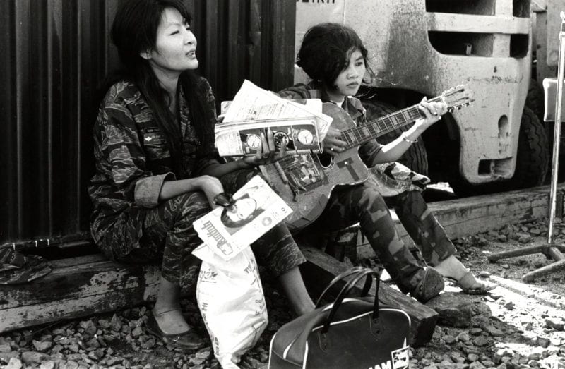 Two women sit with a guitar and a travel bag