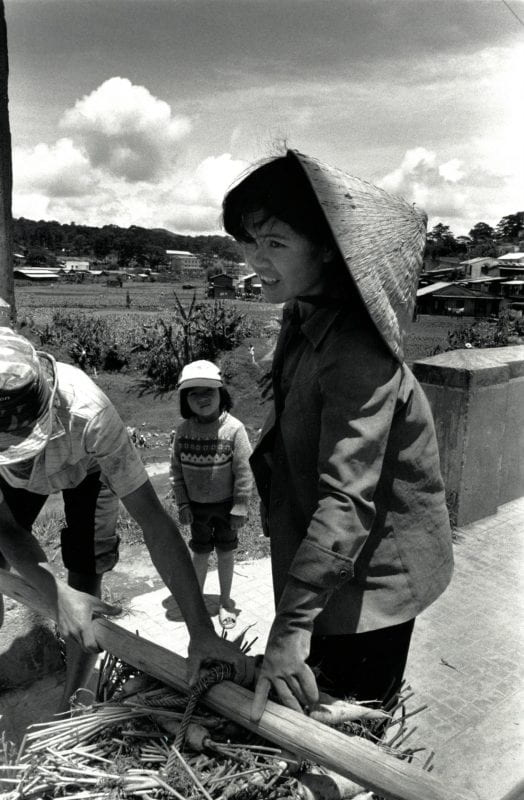 Black-and-white photo of a woman farmer with a man and young child