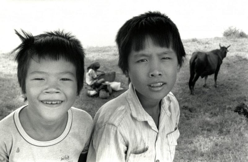 Black-and-white photo of two boys posing in a field in front of a woman and water buffalo