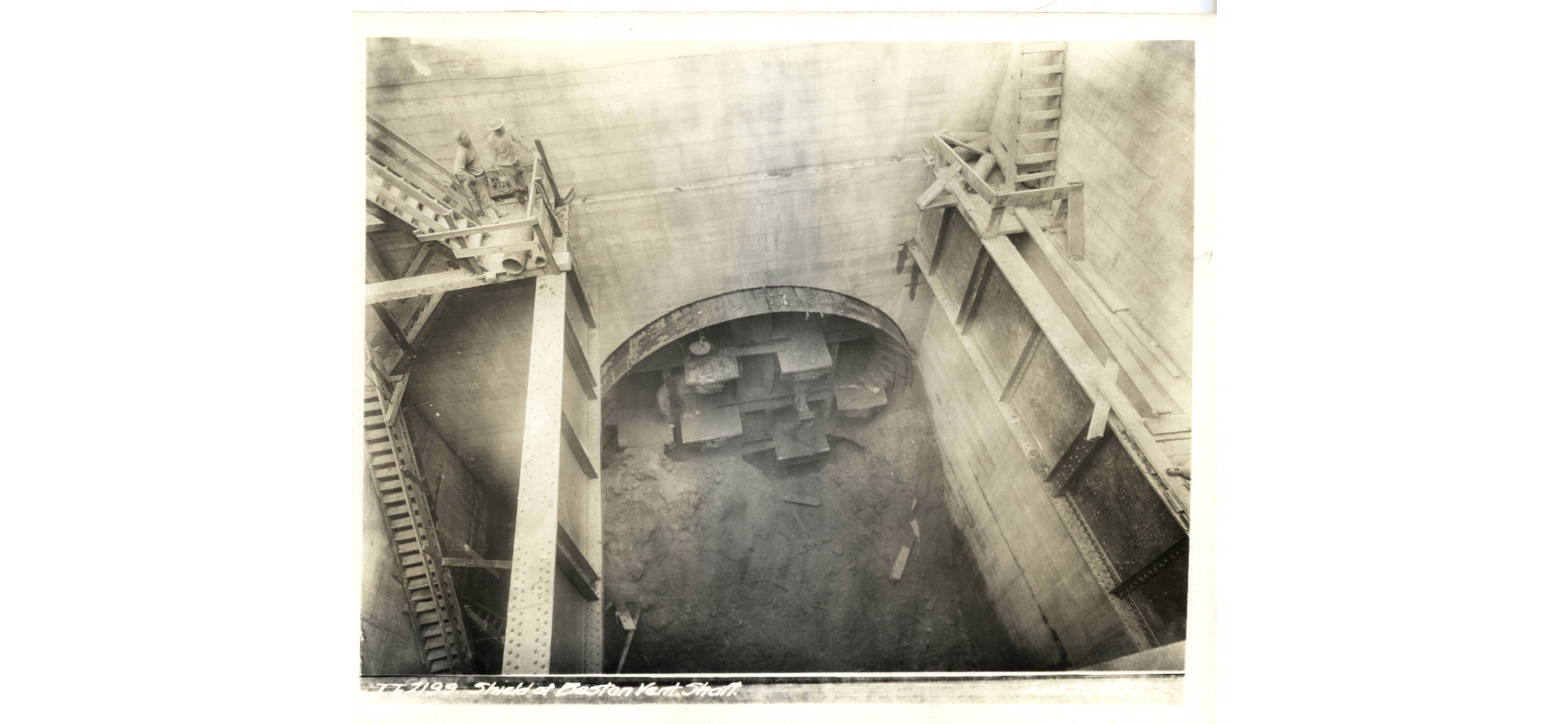Black-and-white photo of the interior of the Boston Vent Shaft, with workers standing on a platform