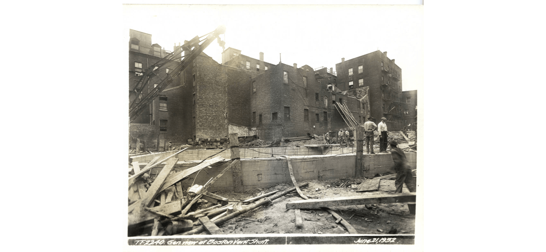 Black-and-white photo of the outside of the Boston Vent Shaft, with workers standing in the foreground and the background