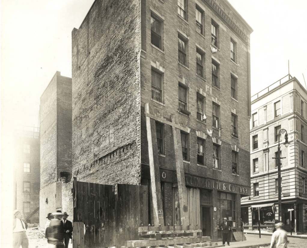 Black-and-white photo of the exterior of the 330 North Street building, with people standing and walking by in the foreground