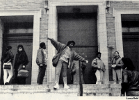 Black and white photographs shows eight students on the steps of a brick school building