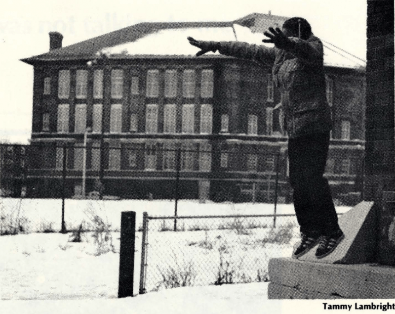 Black and white photograph shows young person with arms up in snow in front of large brick building