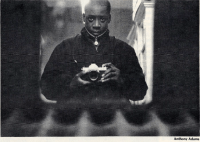 Black and white photographs shows the photographer holding a camera, taking his own picture in a mirror.