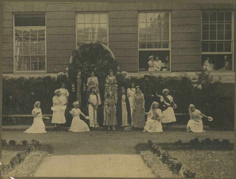 Black-and-white photo of young women performing a play outside of a school building
