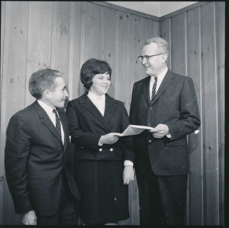 Black-and-white photo of Albert Fulchino and John W. Lederle standing with Audrey Taub