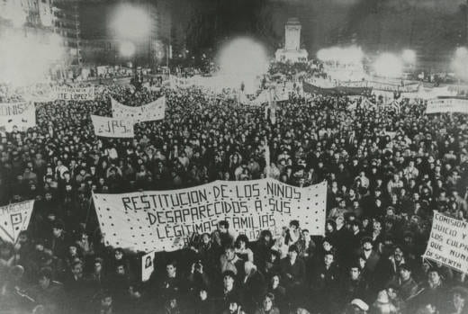 Black-and-white photograph of a large crowd marching in a street