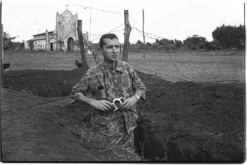 Black-and-white photo of Francois Sully standing in a foxhole holding his camera