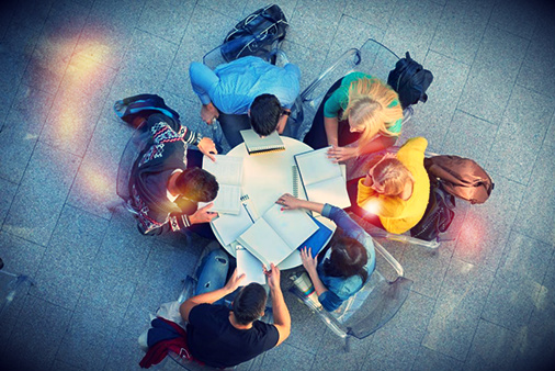 Group of students completing school work together at a round table outdoors
