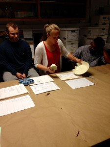 TA Carolyn Horlacher explains the various types of ceramics to students in the field school.