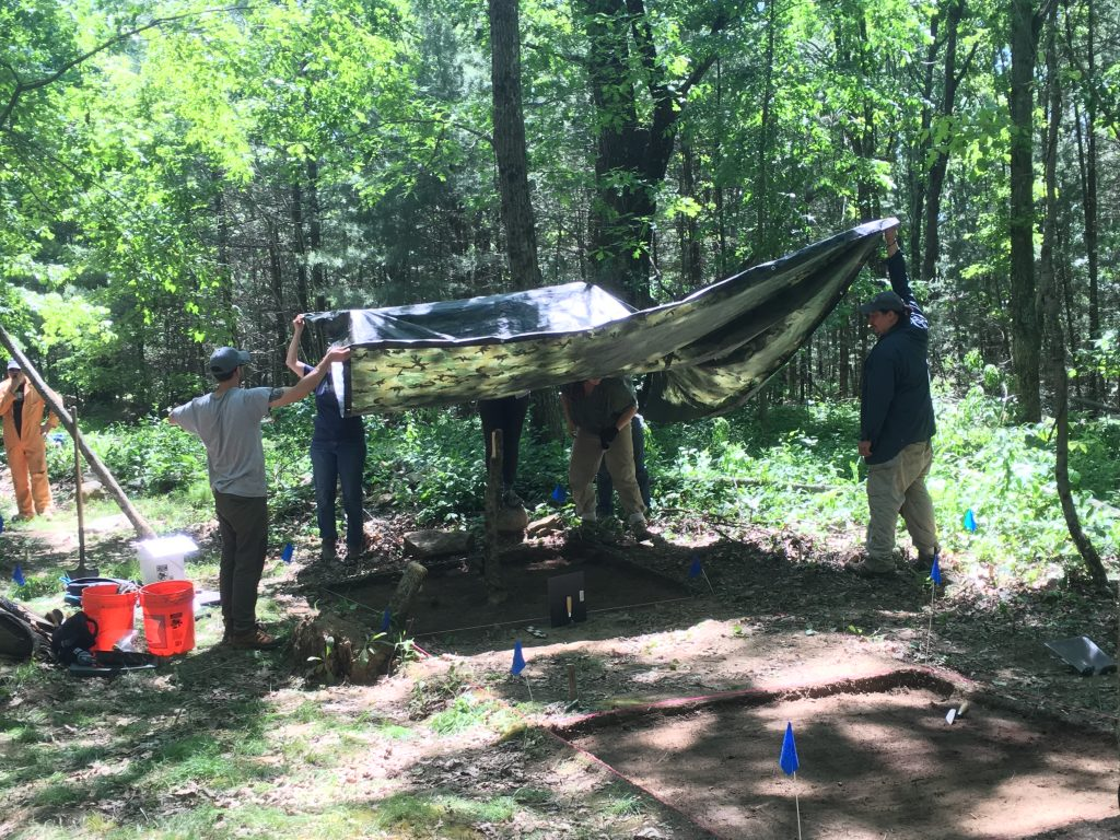 Archaeologists hold a tarp over an open excavation unit in order to take a photo
