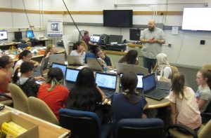 Instructor presents to students sitting at a table with laptops