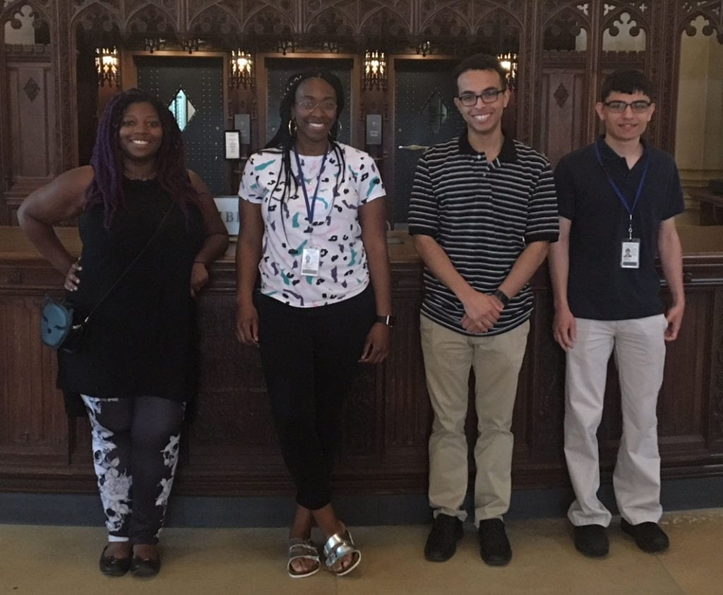 Four smiling students who are interns at Yale University Library though the New Haven Promise program.