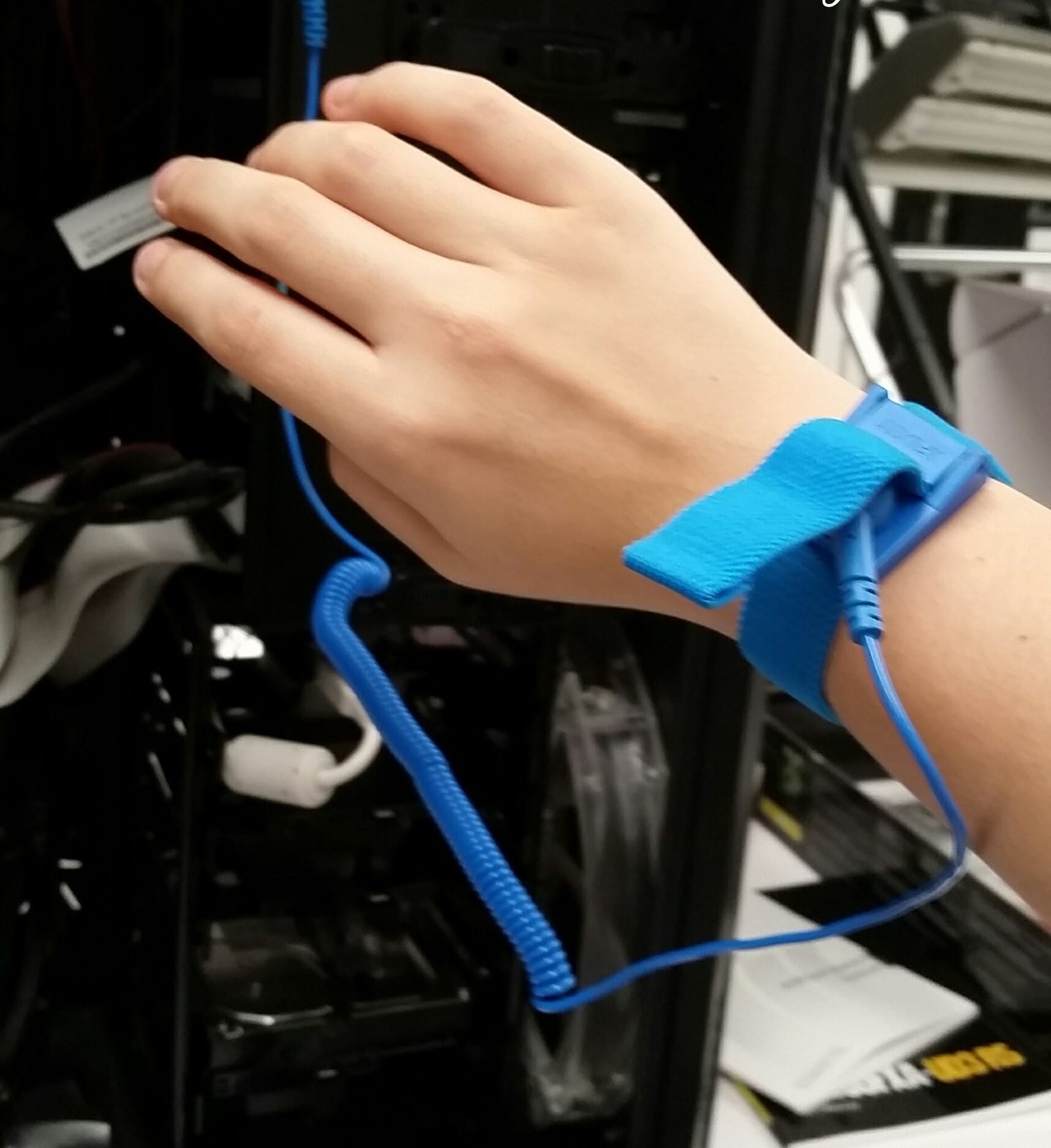 Hand wearing anti-static wristband in front of open computer tower