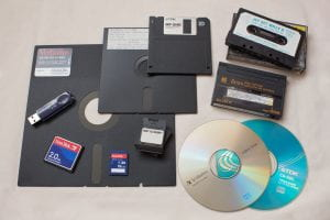 "Image of 11 removable storage technologies laid out on a table: 8"" floppy disk (largest, left; square), 5.25"" floppy disk (next largest, center; square), 3.5"" floppy disk (top center; square), cassette tape (top right, on top of its case; rectangular), 8mm tape (right middle; rectangular), CD (bottom right; round), DVD (bottom right center; round), ZX Microdrive (bottom center; rectangular), SDHC card, CompactFlash card, USB disk (left middle)."