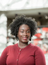 Black woman in red sweater smiling and facing straight ahead