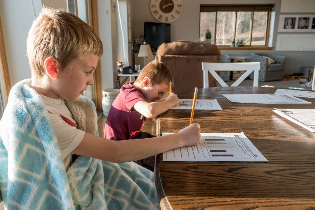 Two kids studying at the kitchen table