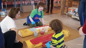 two children kneeling and painting half pipes.