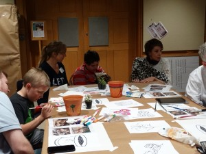 parents and childrens painting flower pots around a table.