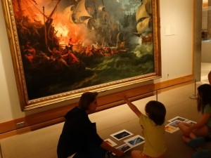 woman and children sitting on floor looking up at large oil painting of ships of fire