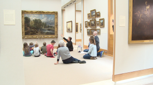 kids and adults sitting on floor looking up at landscape painting