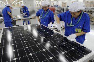 Photo courtesy of econews.com. Chinese workers manufacturing solar panels.