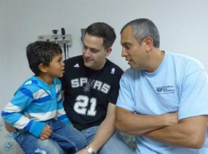 A surgeon from Healing the children meets with a patient and his father.
