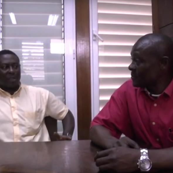 Fotograma del vídeo, muestra tres personas hablando sentadas en una mesa de una oficina/Photo from the video, 2 people speaking while sitting at a table in an office.