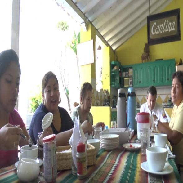 Foto del vídeo, muestra cinco personas desayunando en torno a una mesa en un hotel/Photo from the video, it shows 5 people eating breakfast while sitting at a table in a hotel.