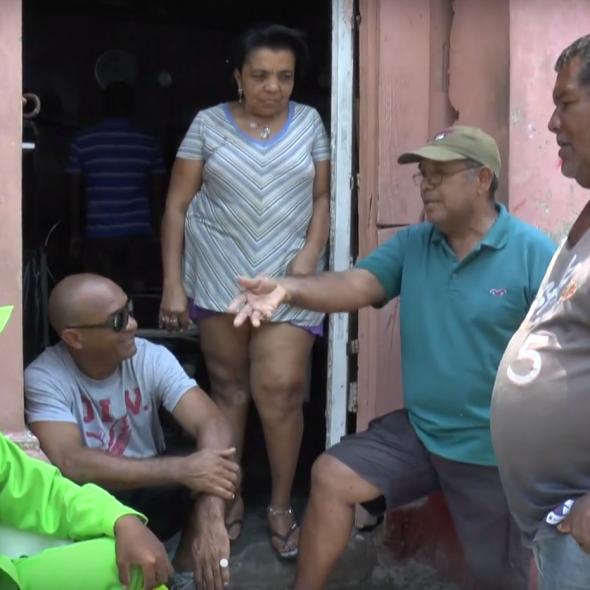 Foto del vídeo, muestra cinco personas hablando en la puerta de una casa/Photo from the video, 5 people speaking at the door of a house