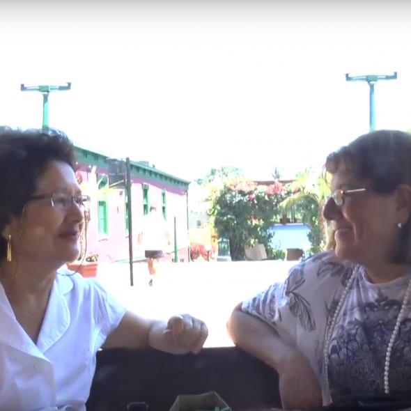Fotograma del vídeo, muestra dos personas hablando en un banco en un parque/Picture form the video, a couple speaking while sitting on a park bench