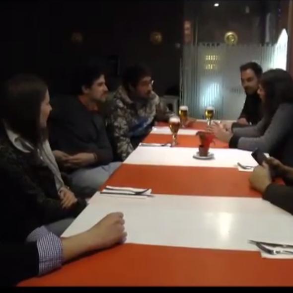 Fotograma del vídeo, muestra ocho personas hablando sentados en una mesa en un bar/Photo from the video, 8 people speaking while sitting at a table in a pub