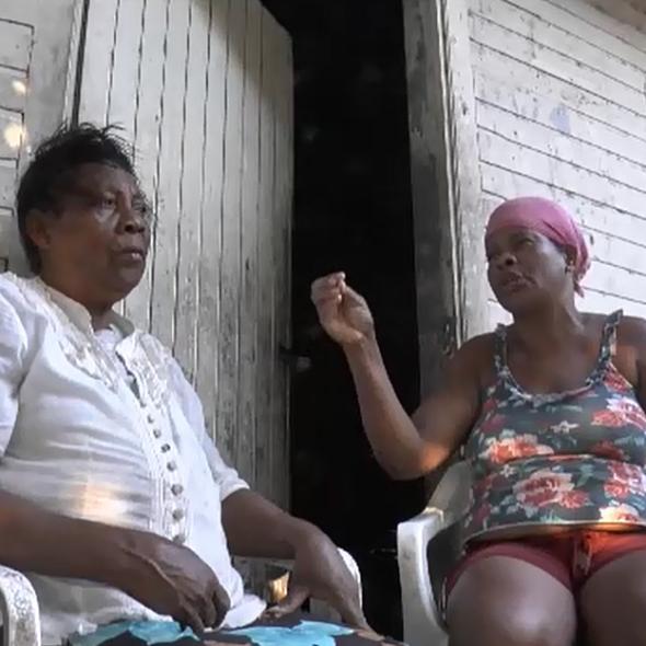 Captura de pantalla del vídeo, 2 mujeres sentadas en la puerta de su casa./Vídeo screenshot, 2 people sitting in front of their house