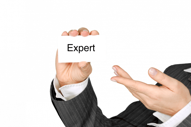 "man holding index card that says ""expert"""