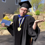 Raskin shrugging while in academic garb.
