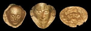 Three Mycenaean masks all of gold.  The middle is the Mask of Agamemnon.  It has much more distinctive features, extended ears, larger eyes, smaller forehead, and a well groomed beard and mustache that is not present on the other two.