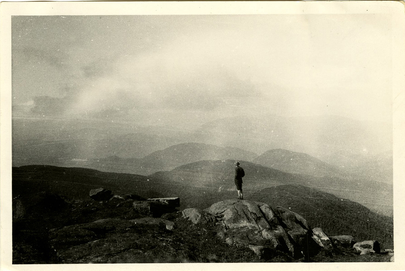 Figure taking in the view of Adirondack peaks from the summit of an unknown mountain, c. 1915.