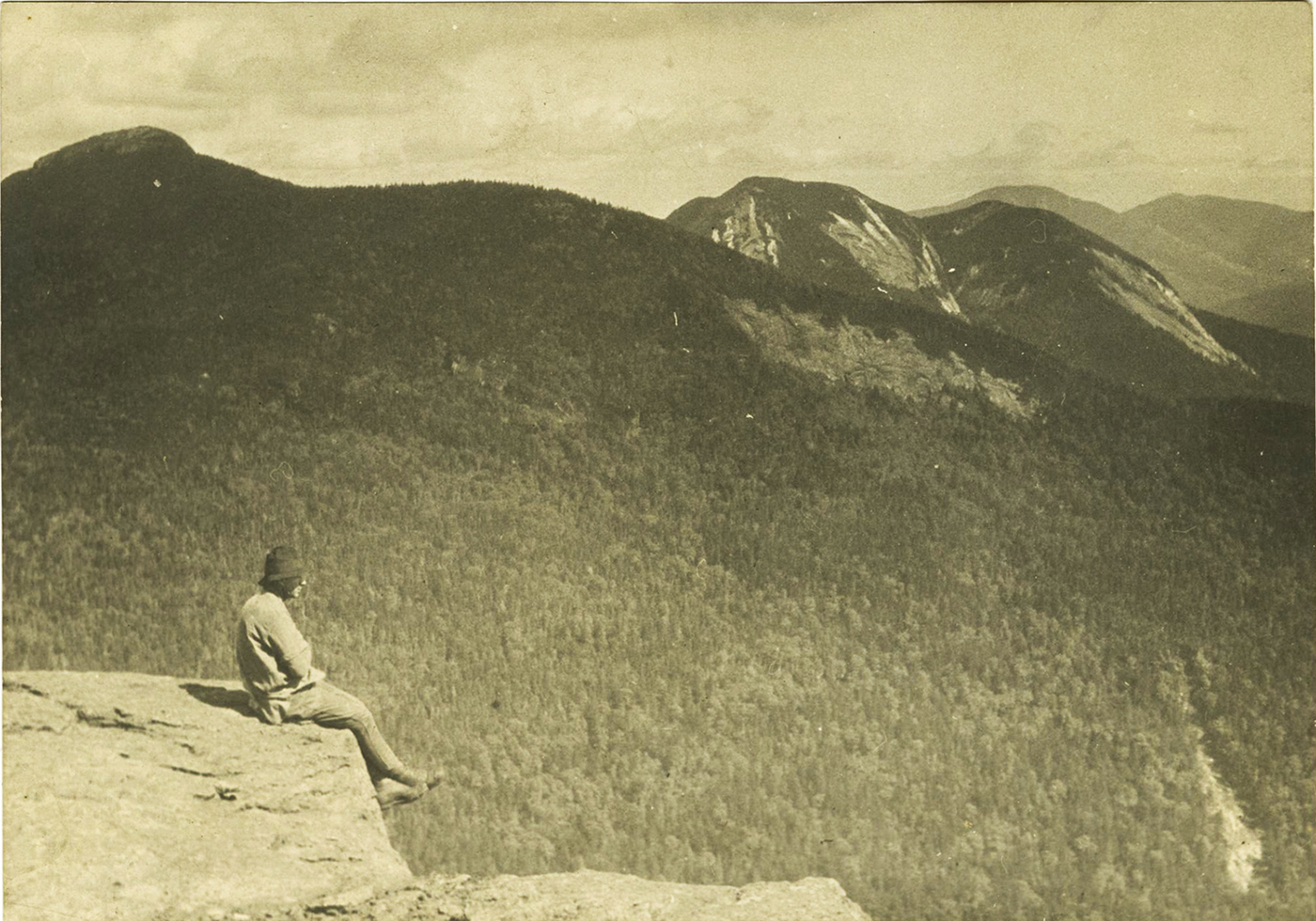 Solitary figure takes in the majestic beauty of the Adirondack mountains, c. 1915.