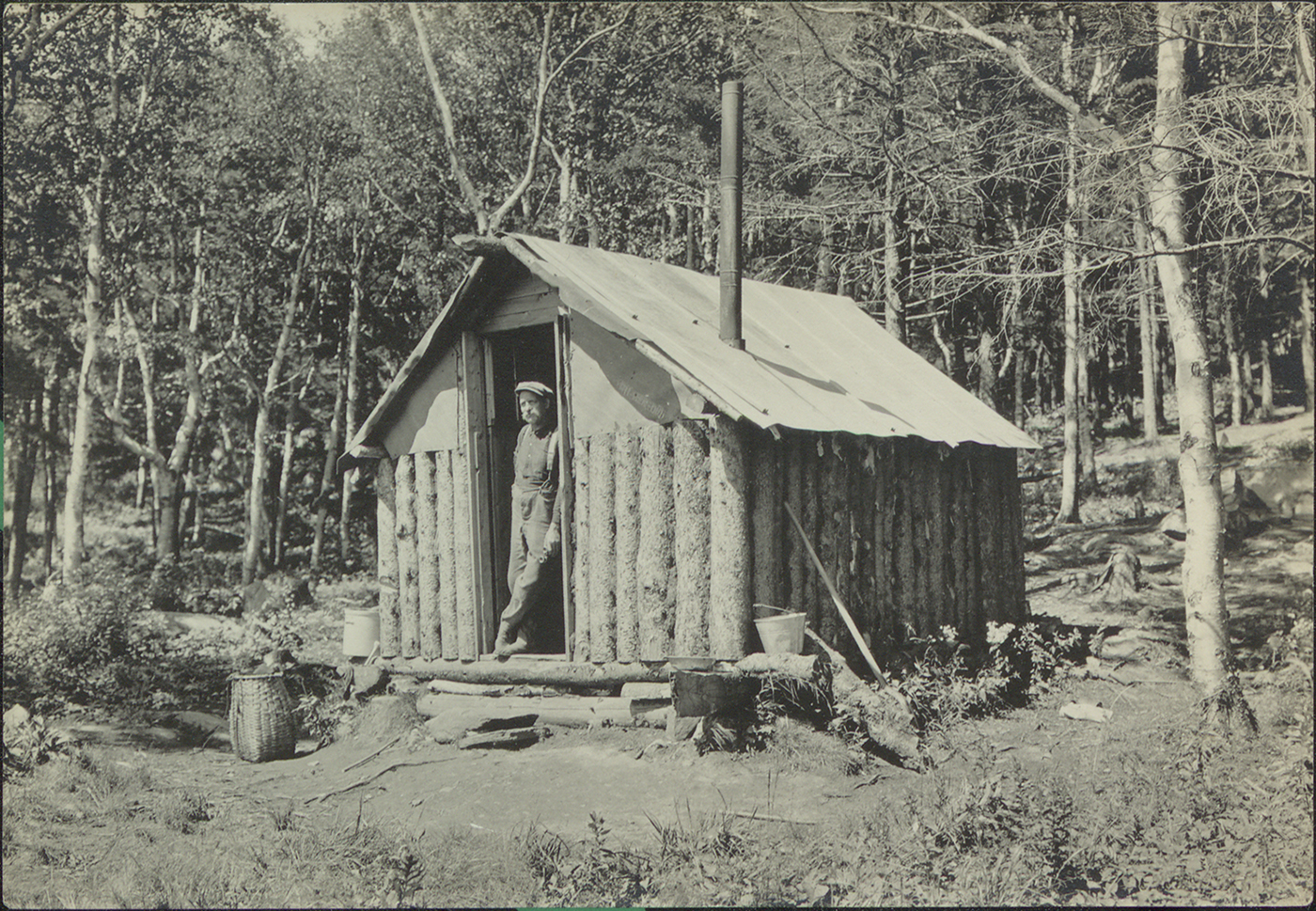 A man leaning against the doorway of an Adirondack a migrant hunting cabin, circa 1915.